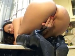 Busty chick apropos leather boots masturbates in a catch kitchen
